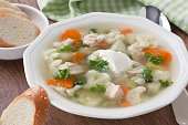 Soup with chicken, cauliflower, vegetable and bread in white plate