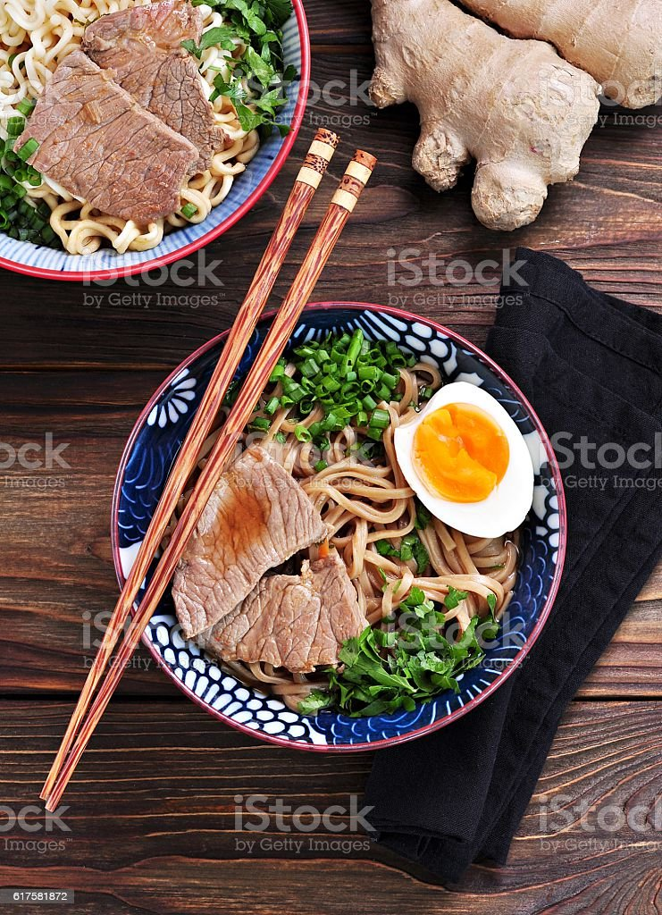 Soup with soba and ramen noodles, beef, ginger, green onions stock photo