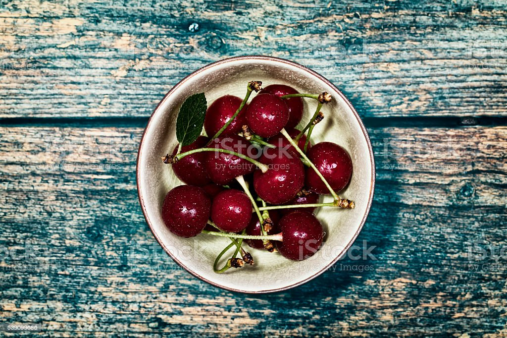 Sour Cherry in Bowl on wood Table stock photo