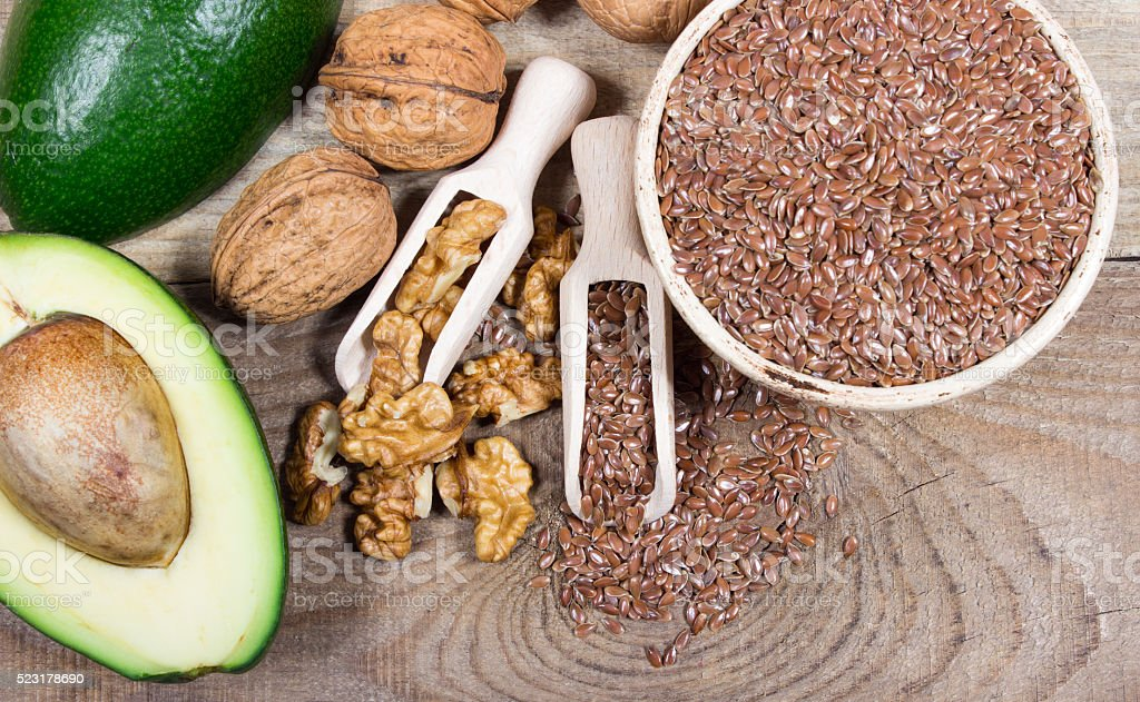 Sources of omega 3 fatty acids: flaxseeds, avocado and walnuts stock photo