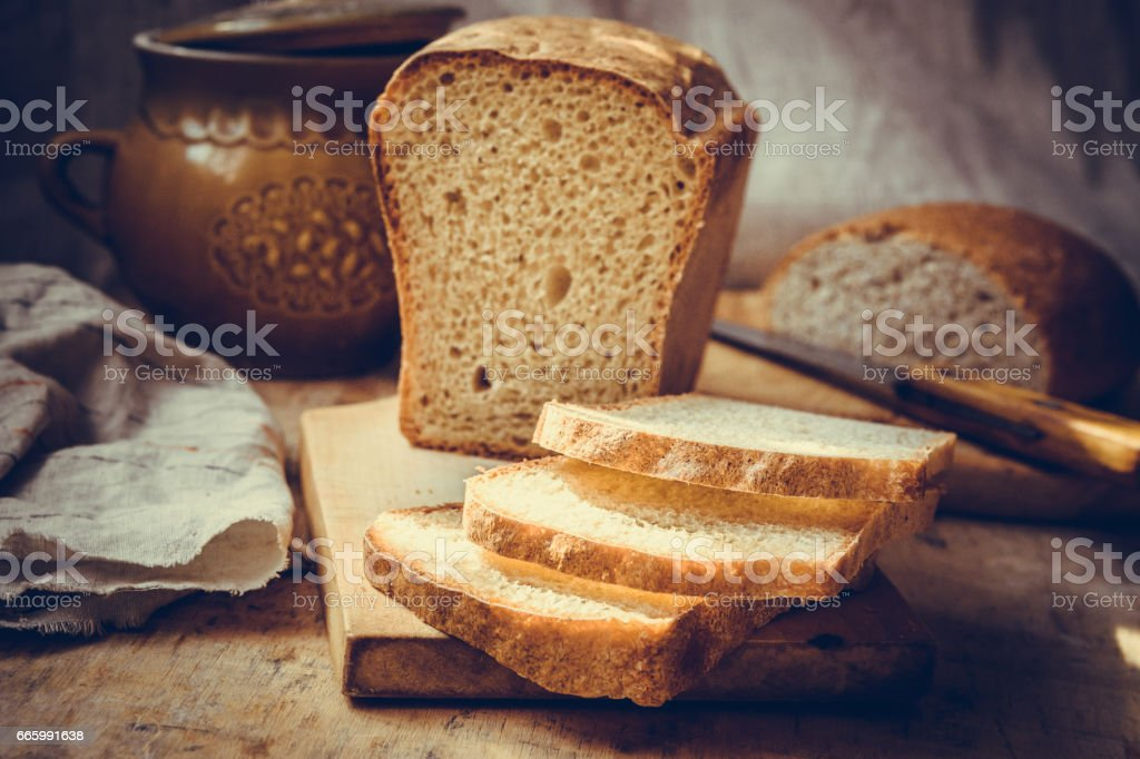 Sourdough bread loaf, sliced on old wood cutting board, vintage crockery, linen towel, authentic rural style, still life stock photo