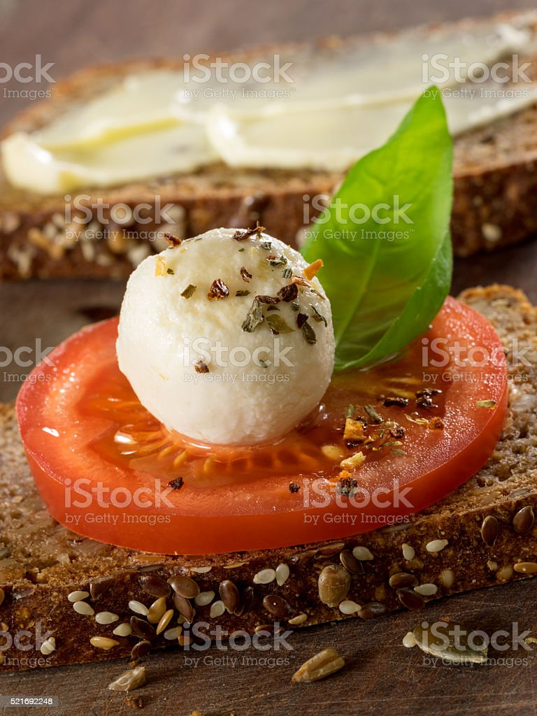 Sourdough rye bread with seeds, butter, cheese and tomato royalty-free stock photo