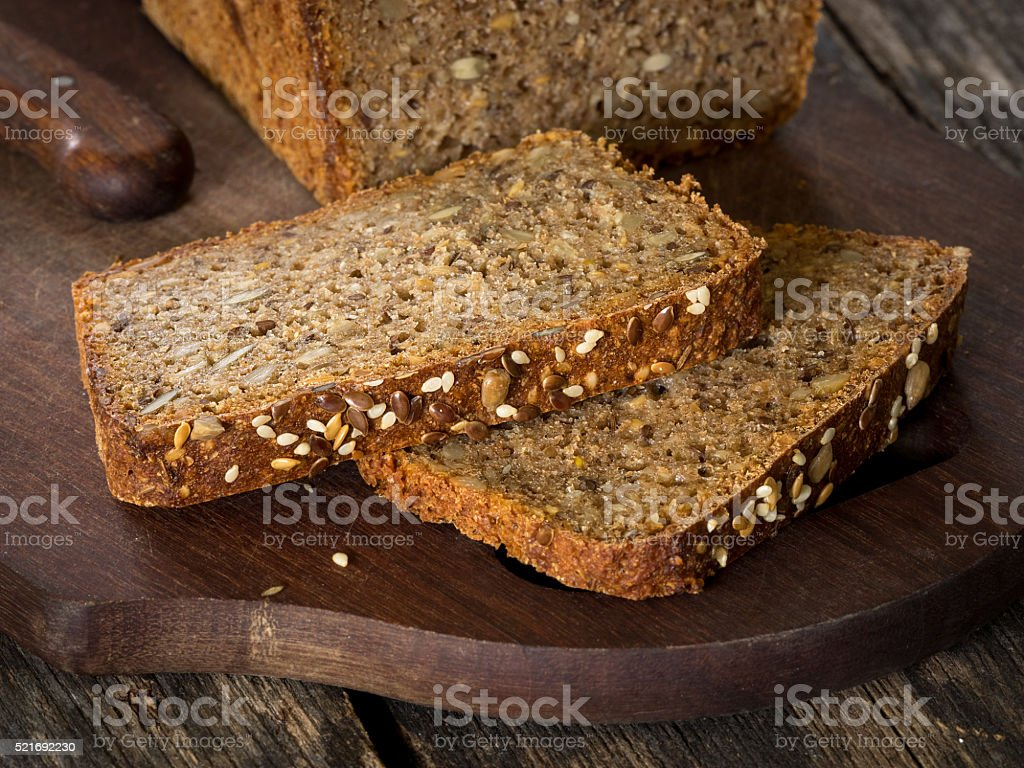 Sourdough rye bread with seeds on a wooden cutting board royalty-free stock photo