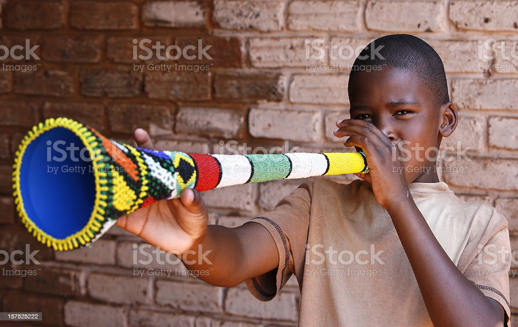 South African boy blowing Vuvuzela royalty-free stock photo