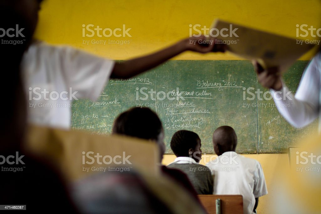 South African teacher hands out books in her classroom stock photo
