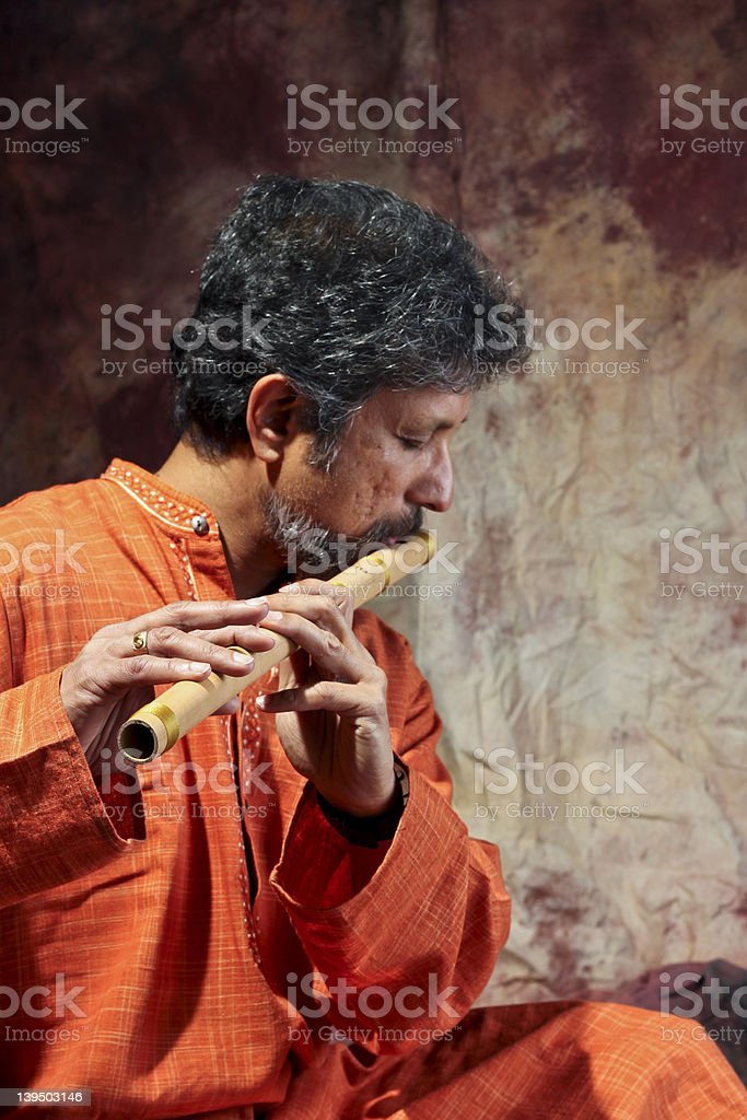 South Asian Man playing flute stock photo