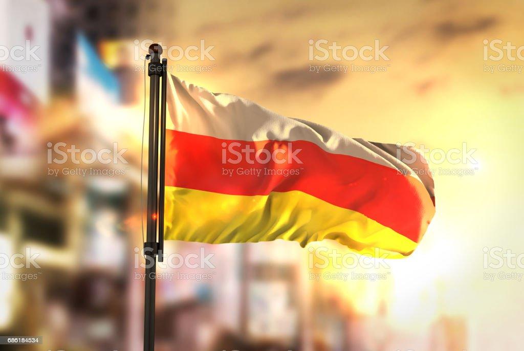 South Ossetia Flag Against City Blurred Background At Sunrise Backlight stock photo