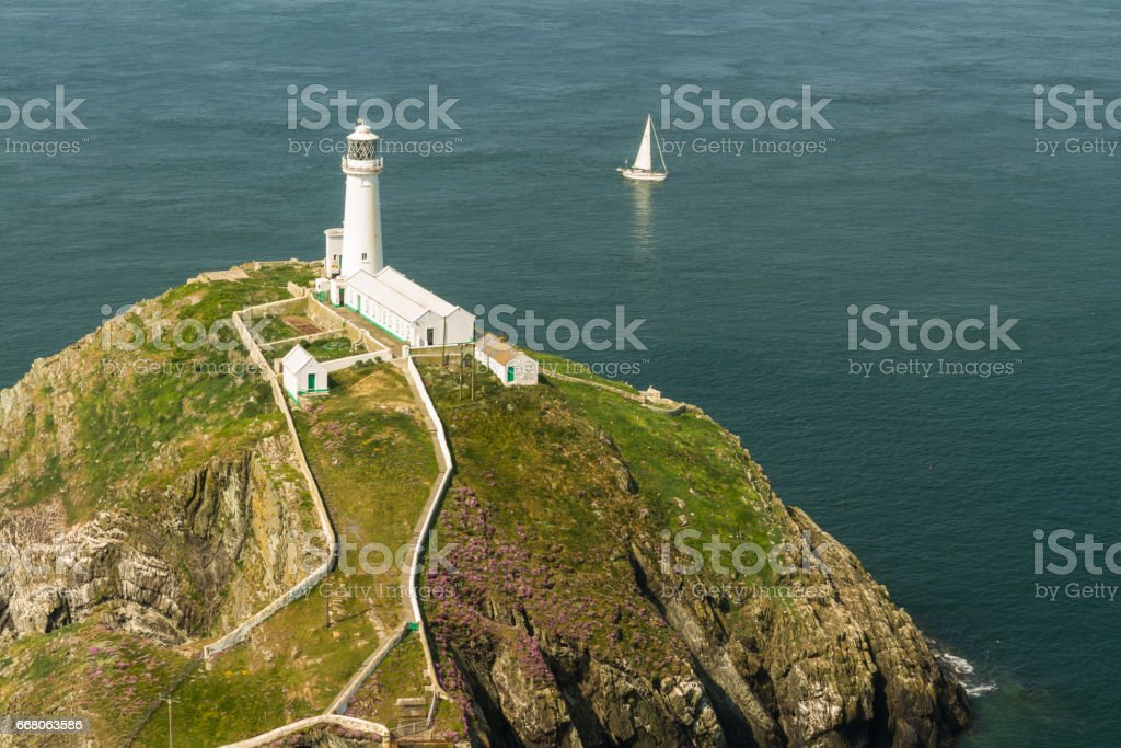 South Stack lighthouse, Anglesey, with white sailing yacht. stock photo
