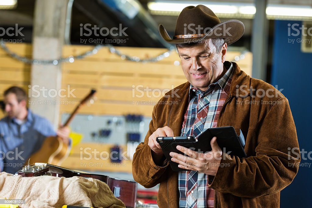 Southern mature man working in musical instrument repair shop stock photo