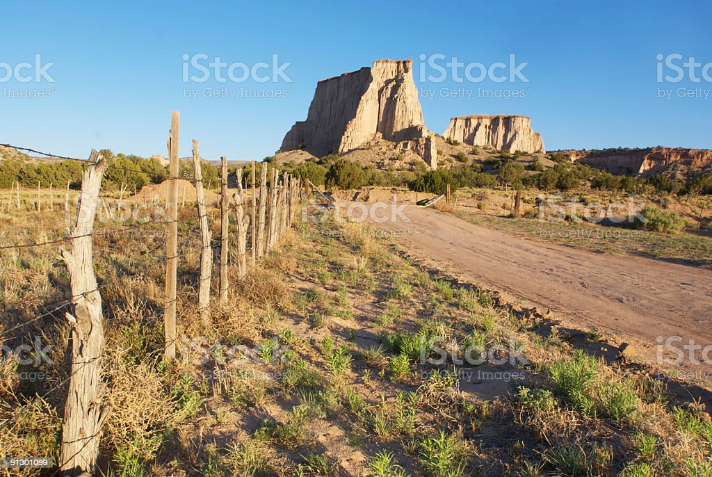 southwestern fence and rock formation landscape stock photo