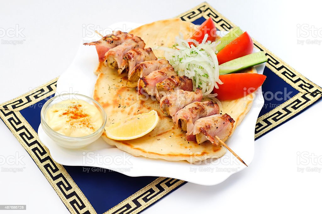Souvlaki, kebab, grilled meat on pita bread with sauce, tomatoes stock photo