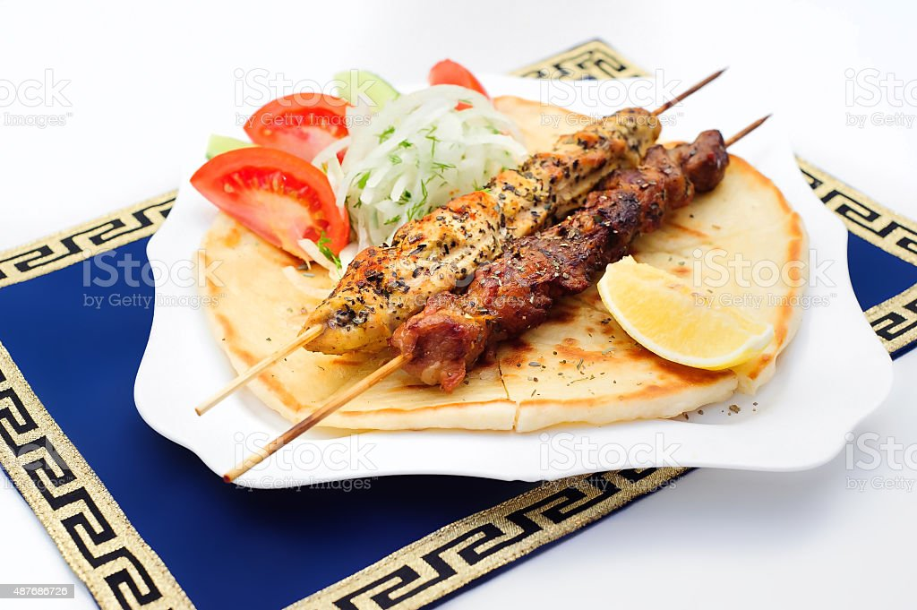 Souvlaki or kebab, grilled meat on pita bread with tomatoes stock photo