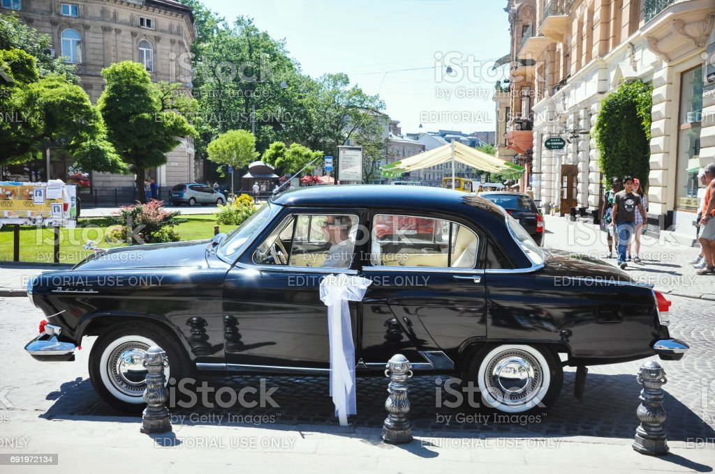Lviv, Ukraine - June 5, 2011: Soviet car 60 years Volga GAZ-21. The driver expects young couple is crowned in the church stock photo