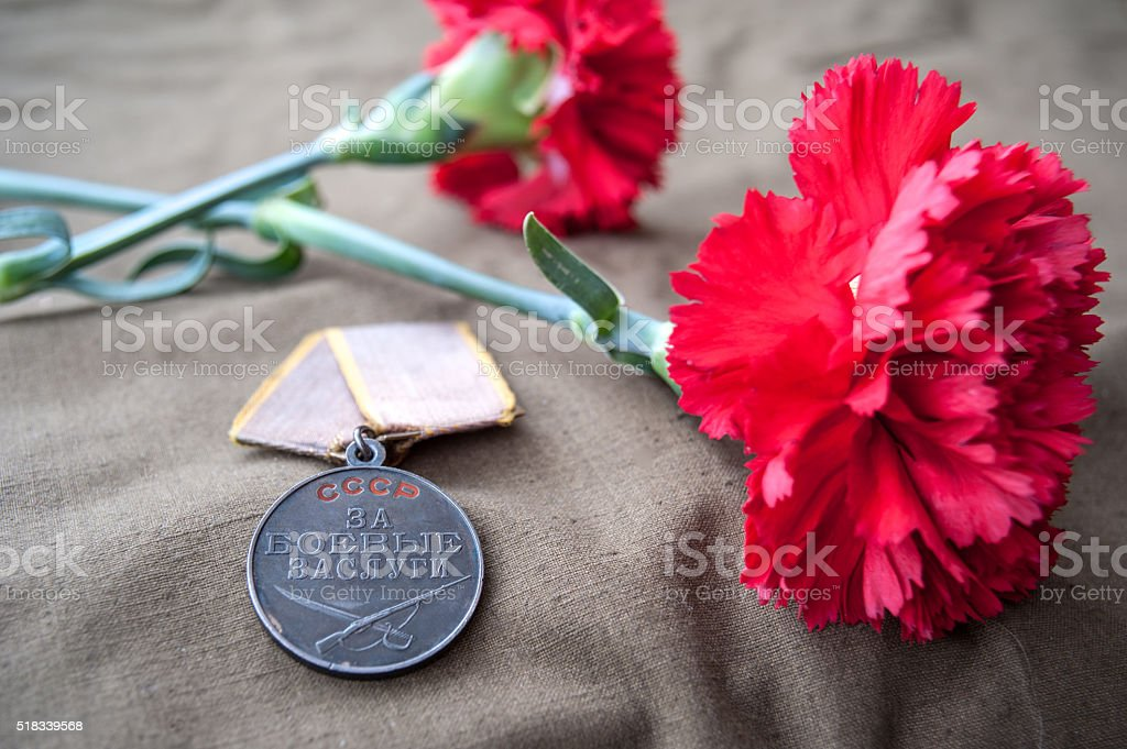 Soviet Medal for Combat Service and two red carnations. stock photo