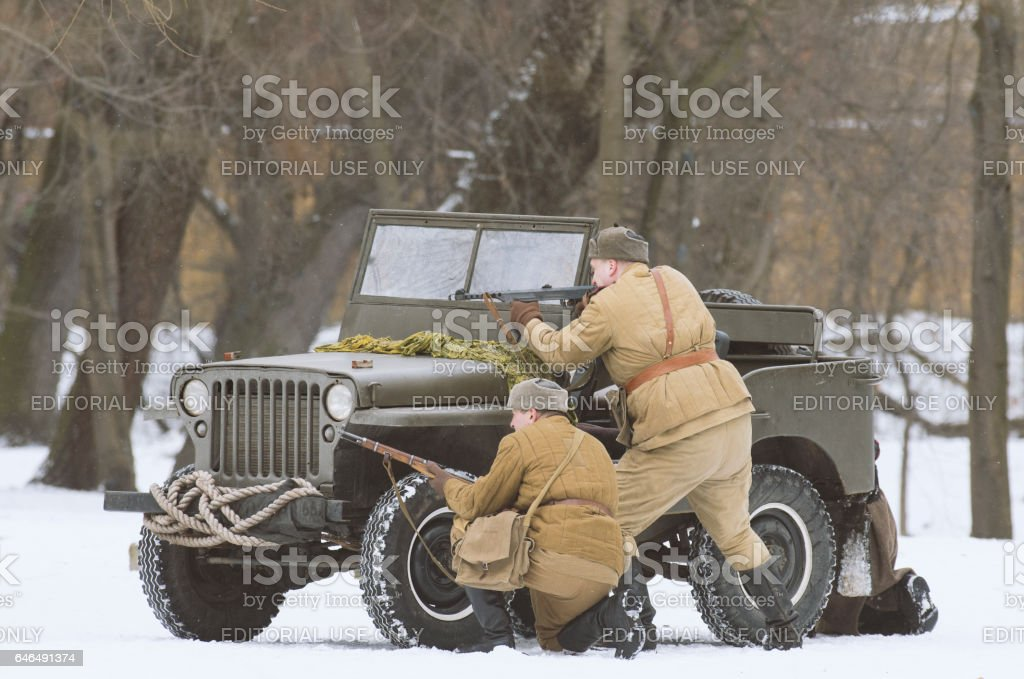 Soviet soldiers hiding behind a jeep Willys, shooting the enemies. stock photo