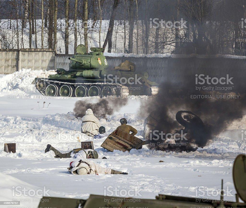 Soviet tank attacking Nazi infantry. Battle reconstruction royalty-free stock photo