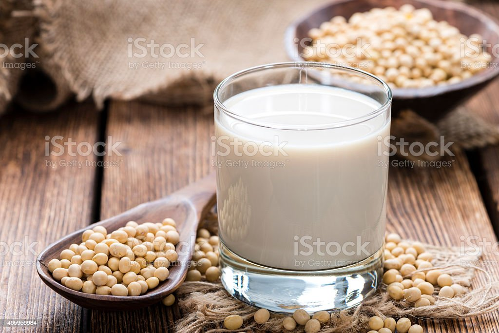 Soy beans on a wooden table with a glass of milk on the side stock photo