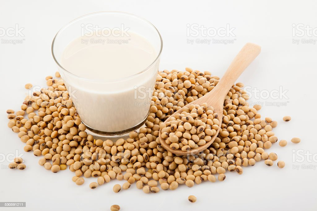 Soy milk in glass with soybeans and wooden spoon stock photo