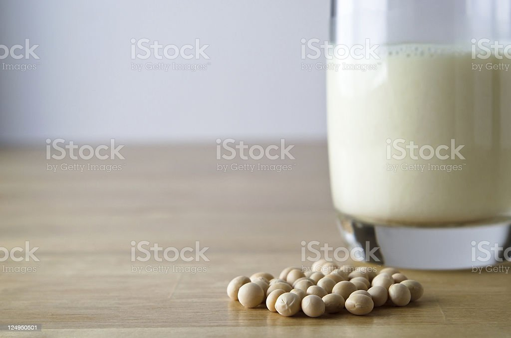 Soya beans next to a glass of soy milk stock photo