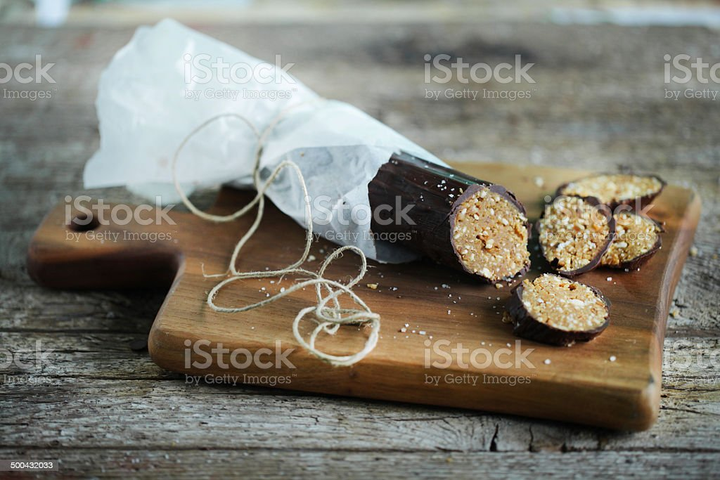 Soya flour chocolate sausage roll cake with nuts, gluten free stock photo