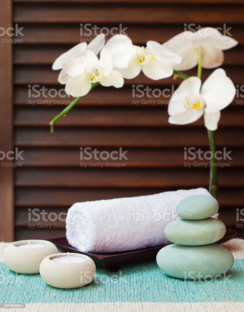Spa and wellness massage setting with candle, towel, stones stock photo