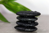 Spa background. Volcanic rock and bamboo with raindrops.