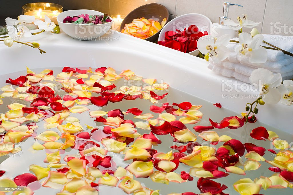 Spa bath with rose petals and candles royalty-free stock photo