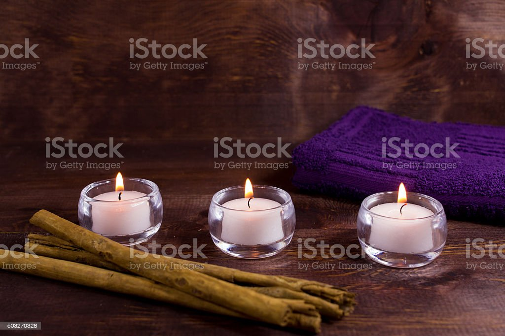 Spa candles with purple towel and cinnamon stock photo