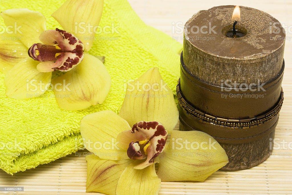 essentials, Vela de spa com orquídeas e toalha amarela foto de stock royalty-free