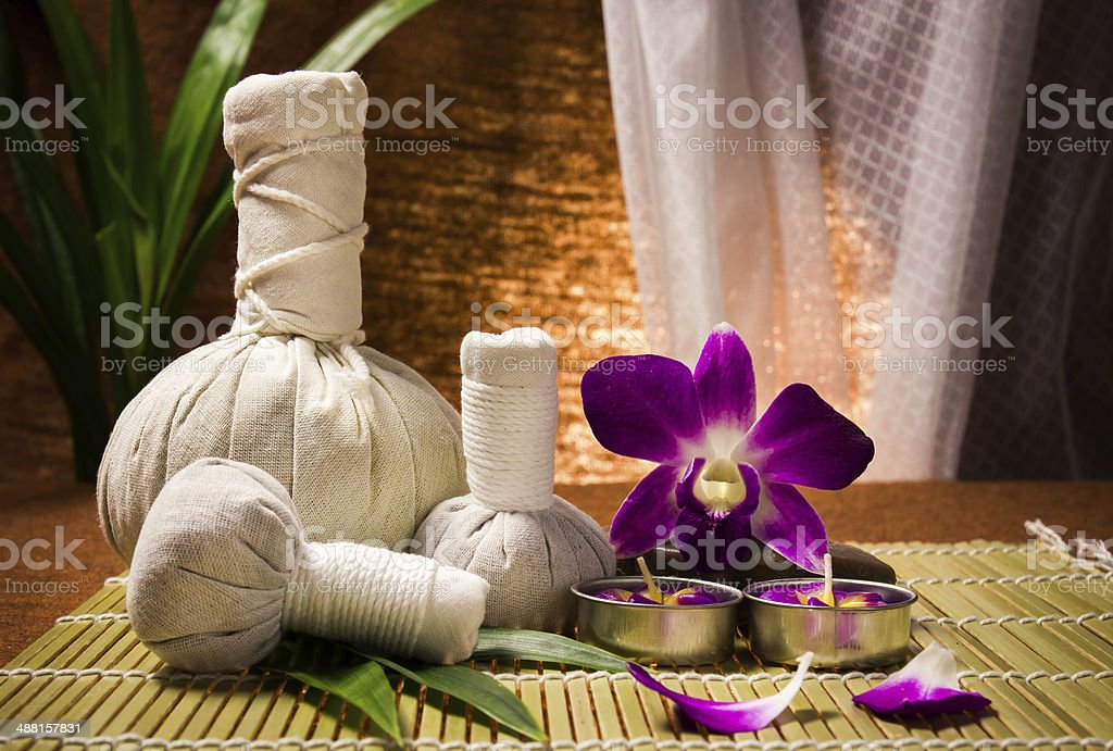 Spa herbal compressing ball with candles and orchid stock photo
