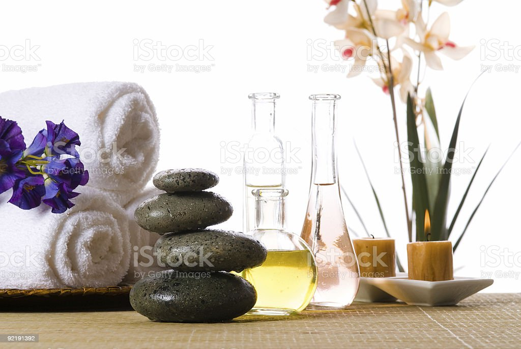 Spa products with stones oils candles and rolled towels royalty-free stock photo