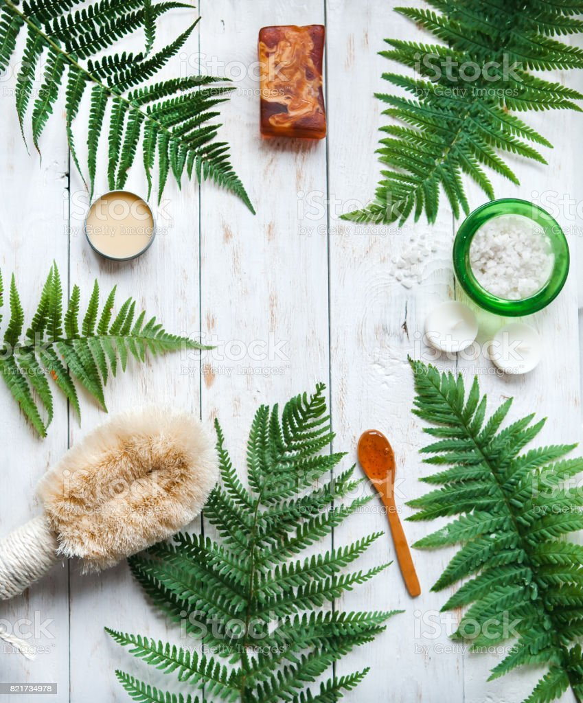 Spa resort and wellness composition.Handmade soap, salt shower, beauty cream with Fern on white wooden background.flat lay stock photo