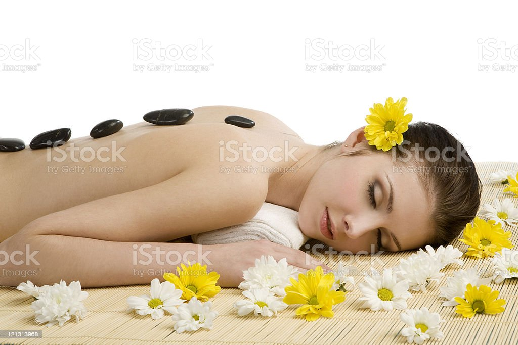 Spa salon: woman relaxing on  mat with flowers and stones. royalty-free stock photo