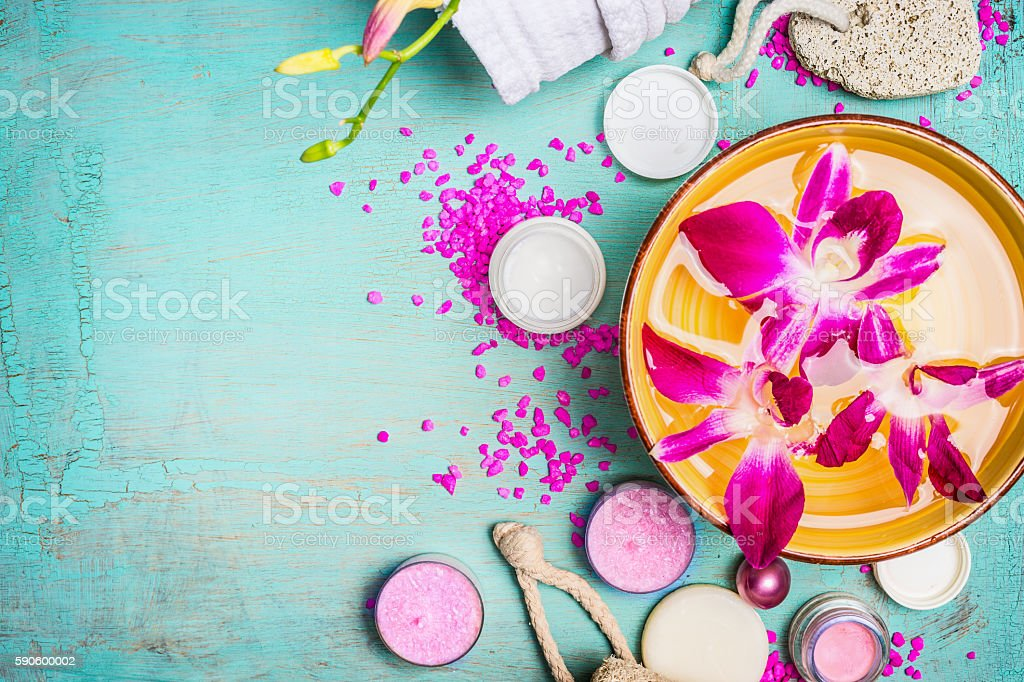 Spa setting with Bowl of water and pink orchid flowers stock photo