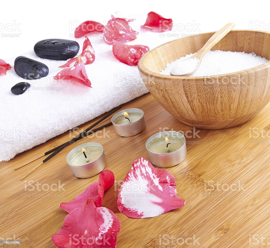 Spa setting with candle, flower red petals, towel and salt royalty-free stock photo