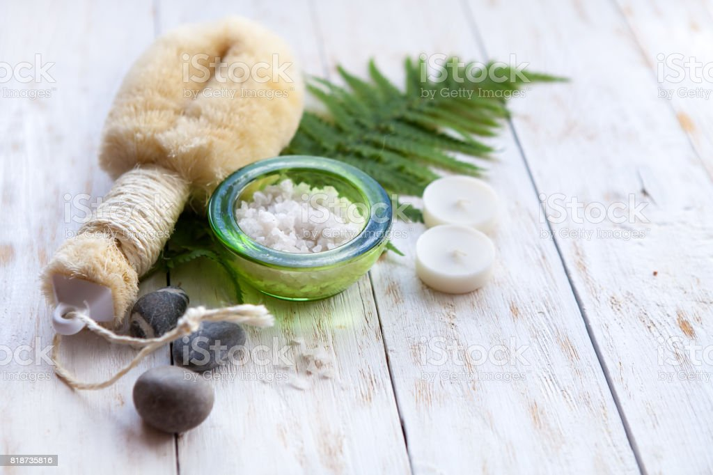 Spa Setting with Washcloth,Natural Soap and Sea Salt with Fern on white wooden background stock photo