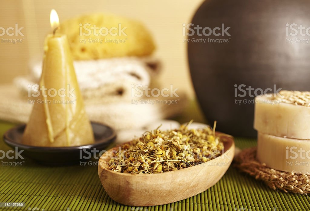 Spa still life of Camomile flowers and candle in bathroom royalty-free stock photo