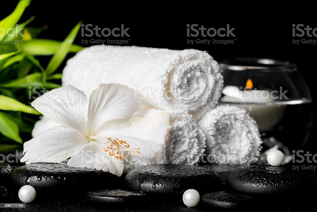 spa still life of white hibiscus flower, bamboo, towels stock photo