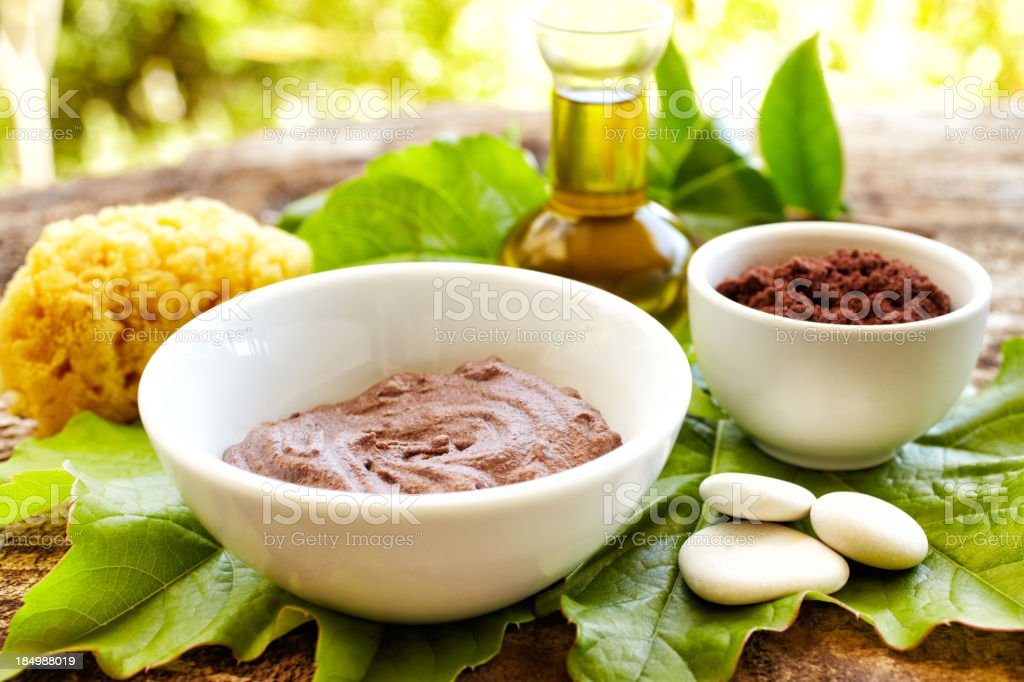 Spa still life with mud mask powder, massage oil outdoors stock photo