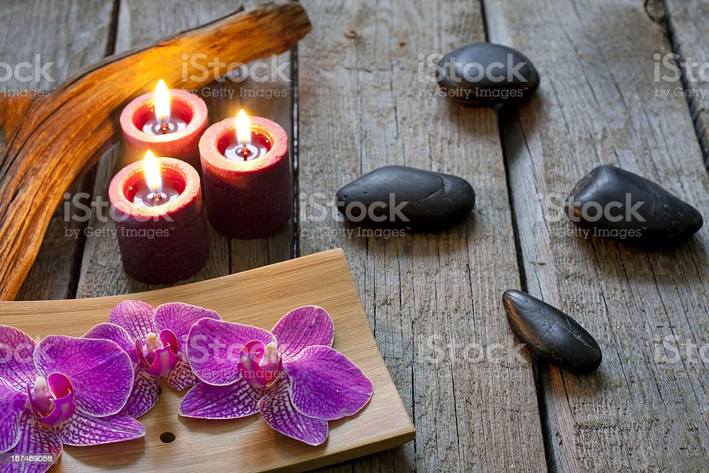 Spa stones orchids and candle on wooden boards royalty-free stock photo