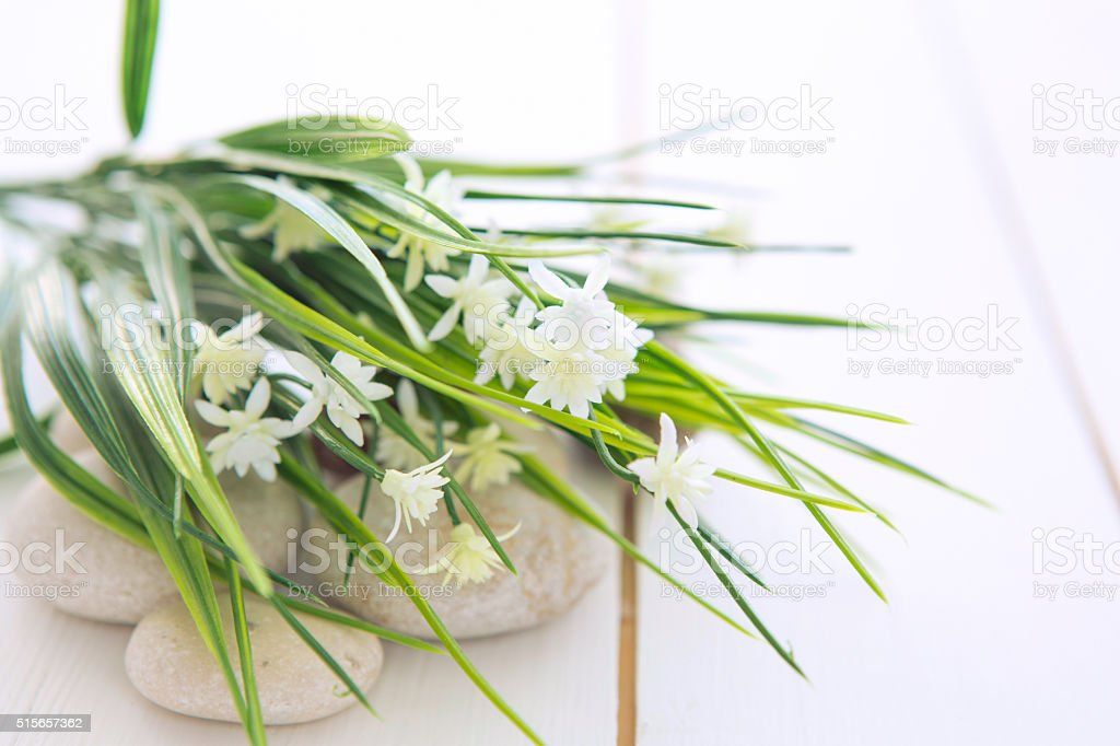 Spa stones with wild flowers on wooden table stock photo