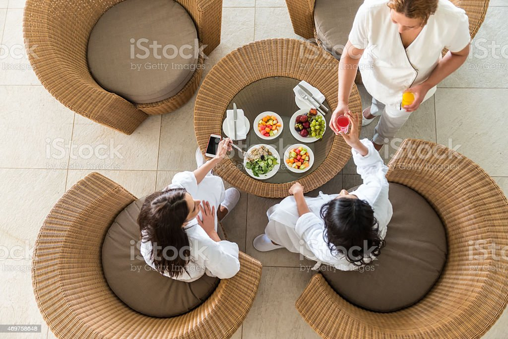 Spa Therapist Serving Fresh Juice to Two Middle Eastern Women stock photo