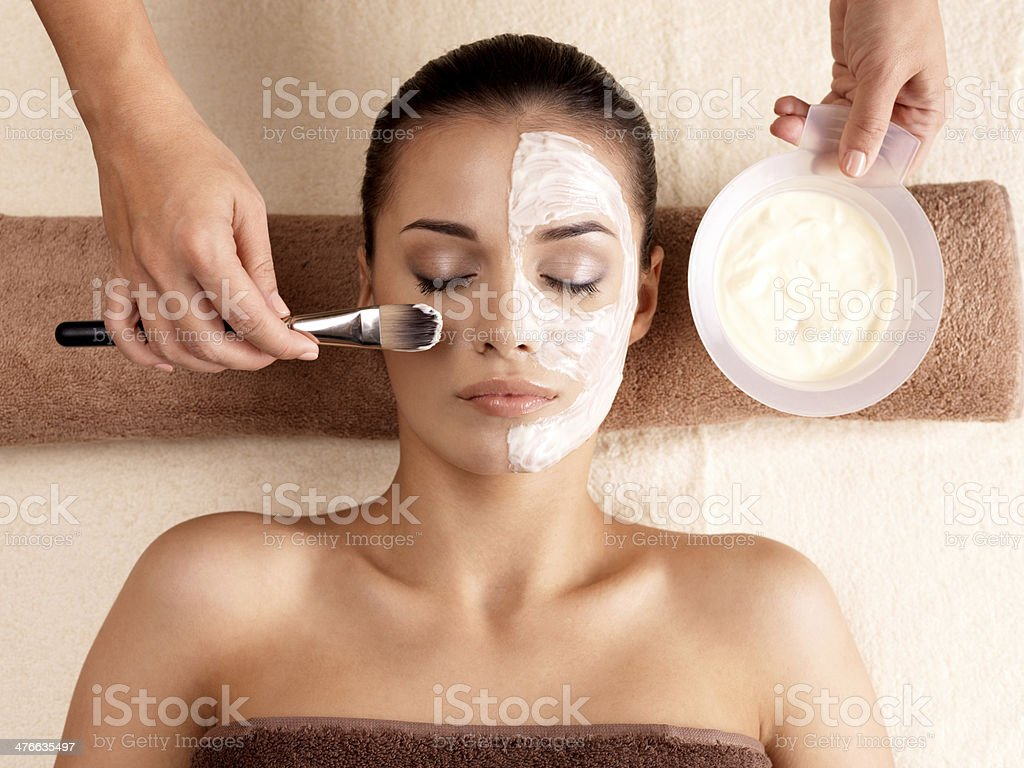 Spa therapy for woman receiving facial mask royalty-free stock photo