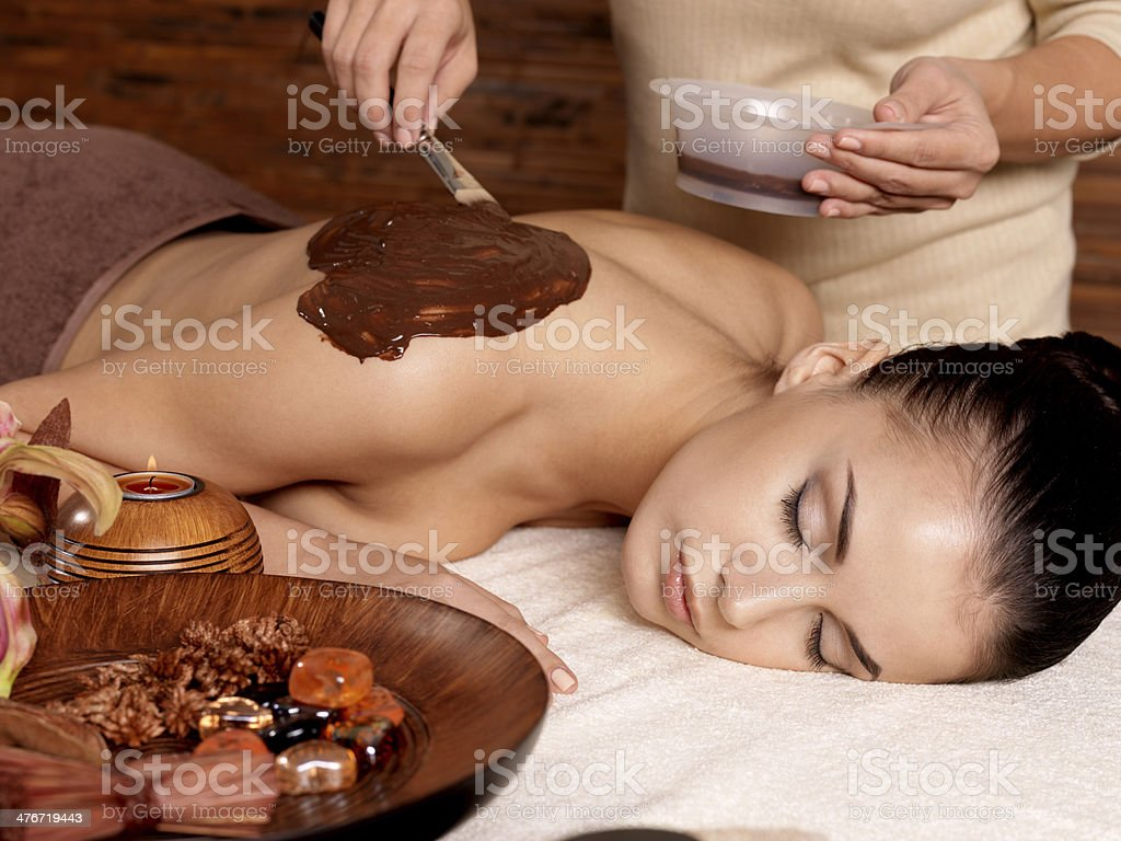 Spa therapy for young woman receiving cosmetic mask royalty-free stock photo