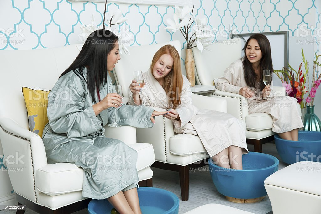 Diverse girlfriends enjoying girls day out at the spa: manicure and...
