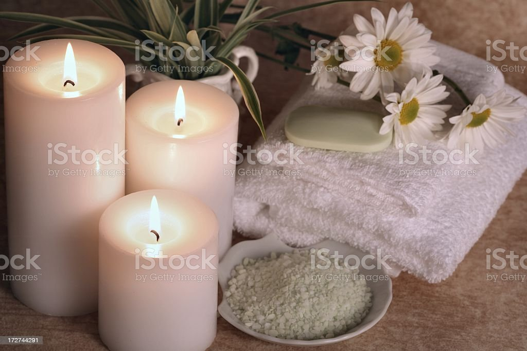 Spa Tranquility with three candles, towels, daisies, soap, salt stock photo