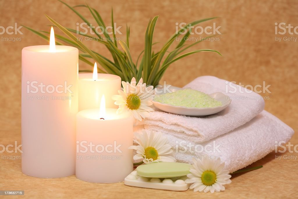 Spa Tranquility with white towels, candles, soap, salts, flowers royalty-free stock photo