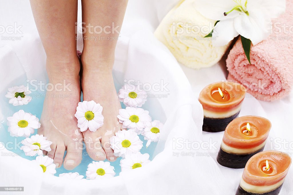 Spa treatment.  Legs in blue water stock photo