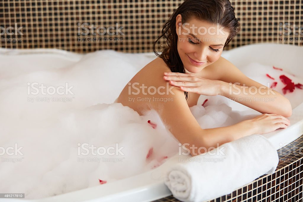 Spa Woman. Beautiful Woman in Bath Cares About Her Hands. stock photo