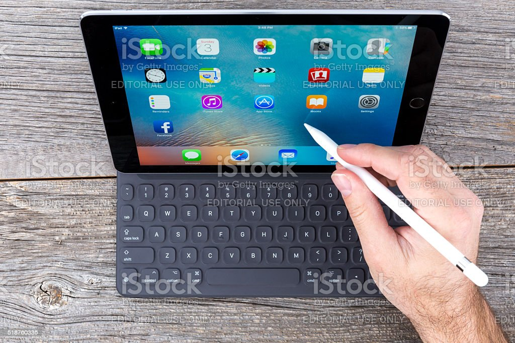 Space Grey iPad Pro Isolated on Wood And Smart Keyboard stock photo